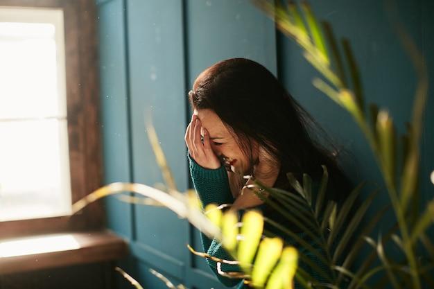Młoda dziewczyna śmieje się głośno wśród zieleni