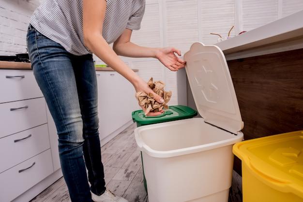 Młoda dziewczyna sortuje śmieci przy kuchnią. pojęcie recyklingu. zero marnowania