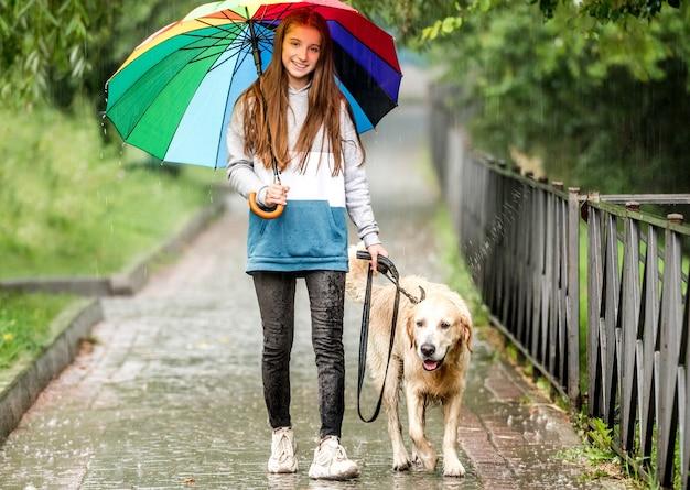 Młoda dziewczyna spacerująca w deszczu z psem golden retriever