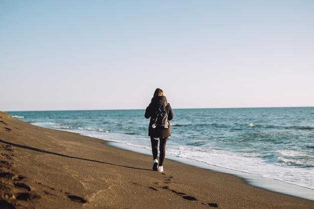 Młoda dziewczyna spaceruje po plaży, w pobliżu morza