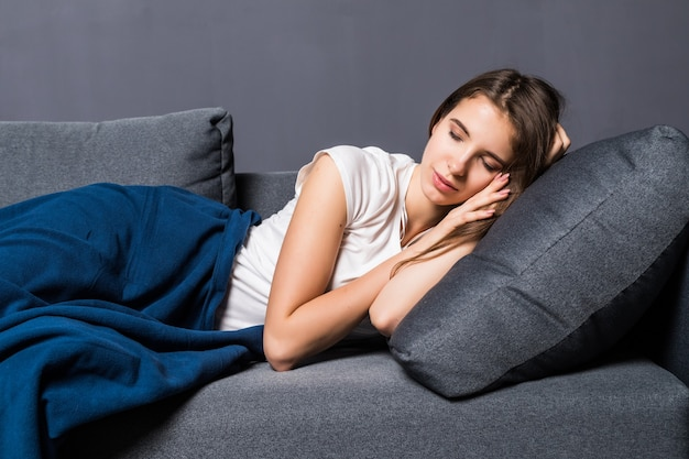 Młoda dziewczyna śpi na kanapie pokrytej niebieskim narzutą na szarym tle