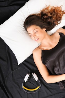 Młoda dziewczyna śpi w łóżku z zestawem słuchawkowym.