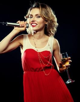 Młoda dziewczyna śpiewa do mikrofonu na imprezie