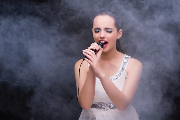 Młoda dziewczyna śpiewa w klubie karaoke