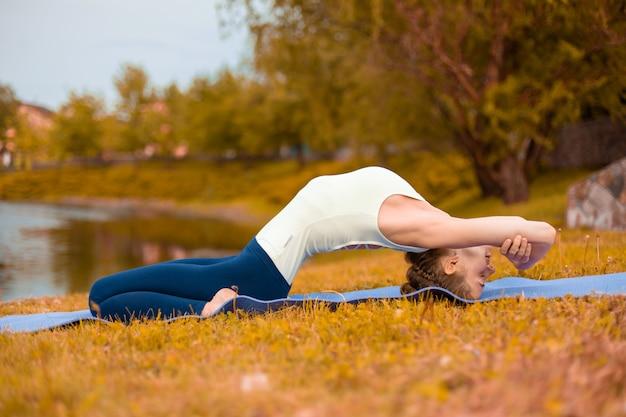 Młoda dziewczyna sportowa ćwiczy jogę na jesiennym żółtym trawniku nad rzeką. medytacja i jedność z naturą