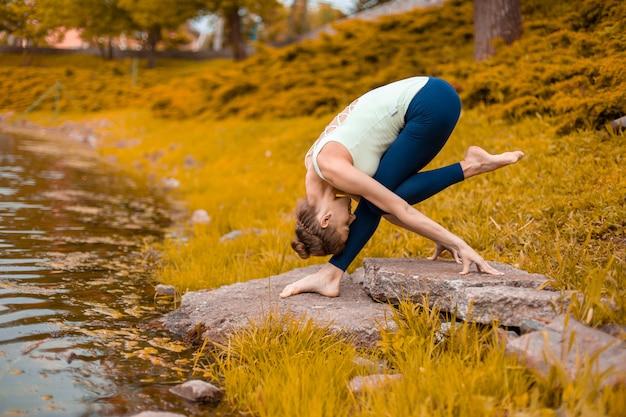 Młoda dziewczyna sportowa ćwiczy jogę na jesiennym żółtym trawniku nad rzeką