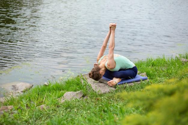 Młoda dziewczyna sportowa ćwiczy jogę na zielonym trawniku nad rzeką, joga zapewnia postawę. medytacja i jedność z naturą