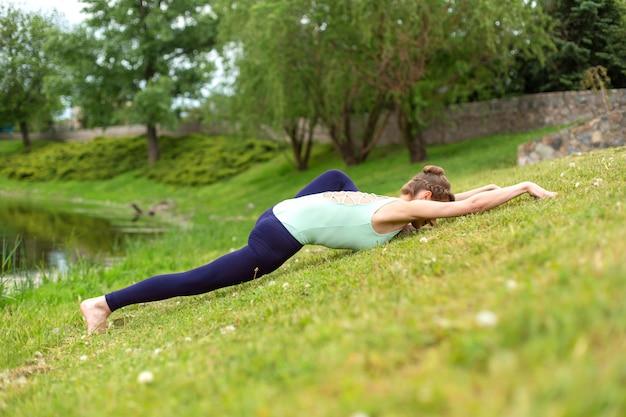 Młoda dziewczyna sportowa ćwiczy jogę na zielonym trawniku nad rzeką, joga zapewnia postawę