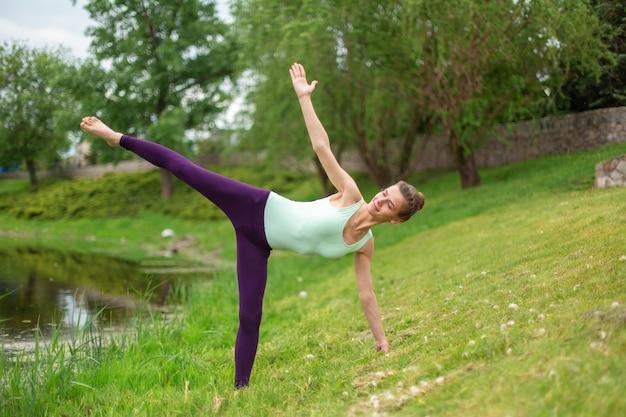 Młoda dziewczyna sportowa ćwiczy jogę na zielonym trawniku nad rzeką