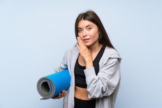 Młoda dziewczyna sportu z matą na izolowanych niebieską ścianą szepcząc coś
