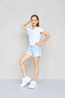 Młoda dziewczyna sprawny w spodenki t-shirt i dżinsy pozowanie w studio