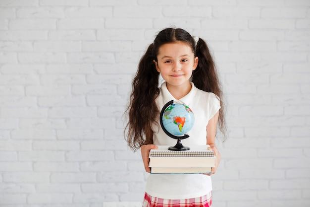 Młoda dziewczyna stałego gospodarstwa książek globu