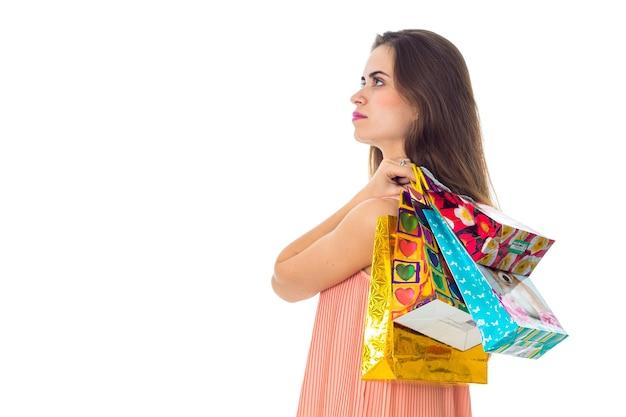 Młoda dziewczyna stoi bokiem i trzyma torby na ramię z zakupami w zbliżeniu