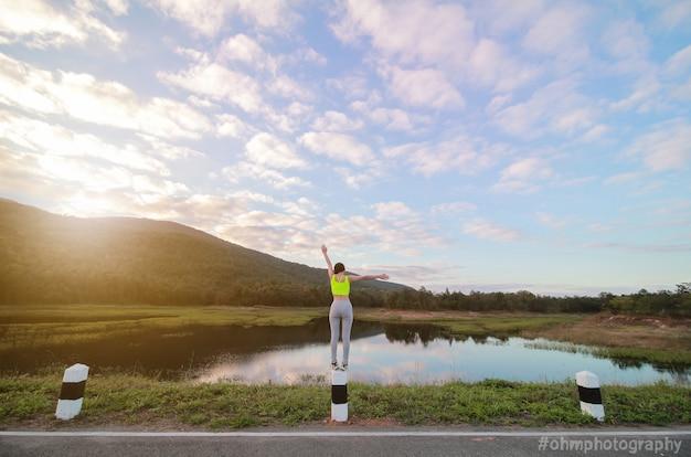 Młoda dziewczyna stoi na stronie rzeki