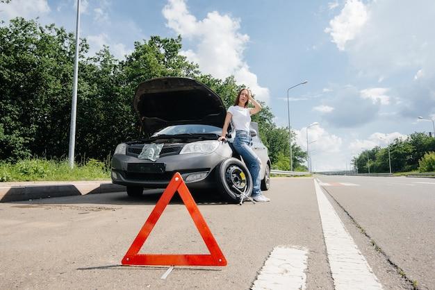 Młoda dziewczyna stoi obok zepsutego samochodu ze złamanym kołem na środku autostrady i sfrustrowana czeka na pomoc w upalny dzień. awaria i awaria samochodu. czekam na pomoc.