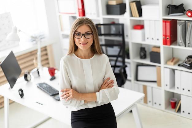Młoda dziewczyna stoi oparty o stół w biurze.