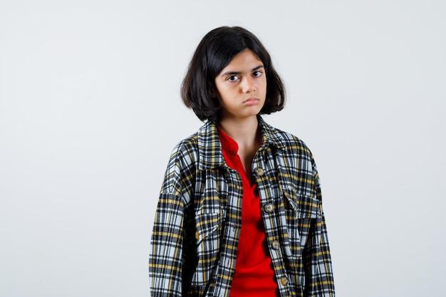 Młoda dziewczyna stoi prosto i pozowanie do kamery w kraciastej koszuli i czerwonej koszulce i wygląda poważnie. przedni widok.