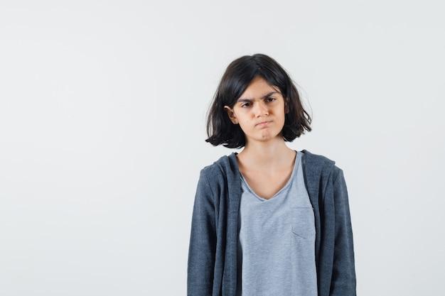 Młoda dziewczyna stoi prosto i pozuje do kamery w jasnoszarym t-shircie i ciemnoszarej bluzie z kapturem na zamek i wygląda poważnie.