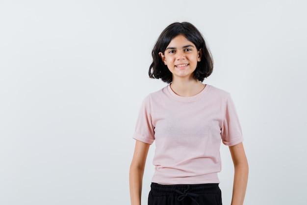 Młoda dziewczyna stoi prosto i pozuje do kamery w różowej koszulce i czarnych spodniach i wygląda na szczęśliwą