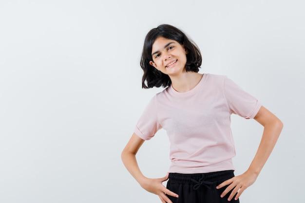 Młoda dziewczyna stoi prosto, trzymając się za ręce w talii i pozuje do kamery w różowej koszulce i czarnych spodniach i wygląda na szczęśliwą
