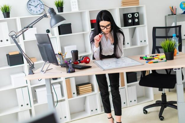 Młoda dziewczyna stoi przy biurku komputerowym i rysuje marker na tablicy magnetycznej.