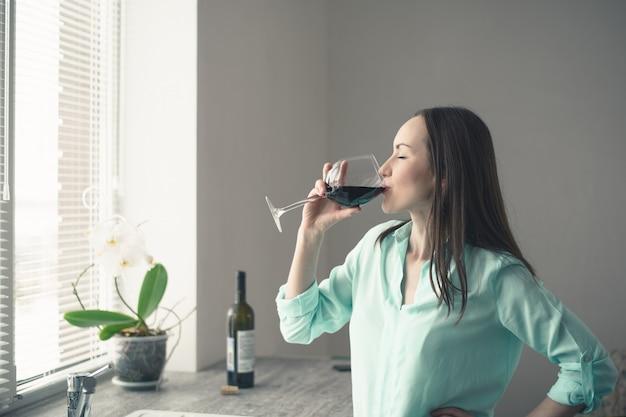 Młoda dziewczyna stoi przy oknie w kuchni i pije z kieliszka czerwonego wina
