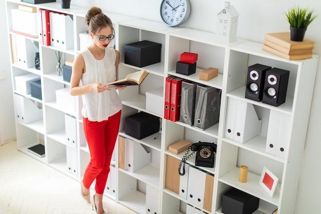 Młoda dziewczyna stoi przy półce i trzyma w rękach otwartą książkę.