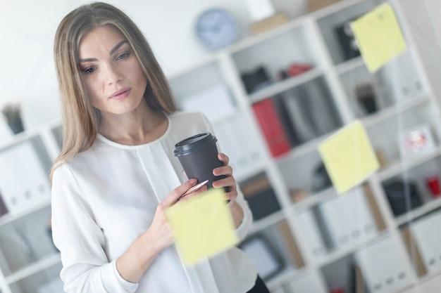 Młoda dziewczyna stoi przy przezroczystej planszy z naklejkami i trzyma szklankę z kawą i długopisem.