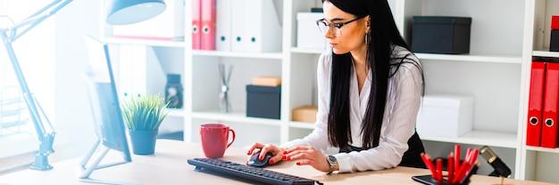 Młoda dziewczyna stoi przy stole i drukuje na klawiaturze. obok dziewczyny są dokumenty.