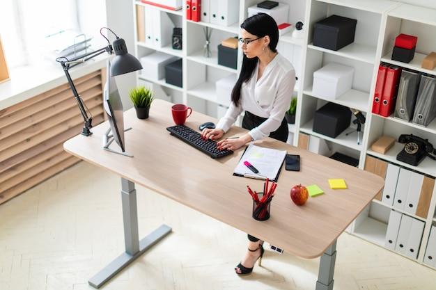 Młoda dziewczyna stoi przy stole i pisze tekst na klawiaturze