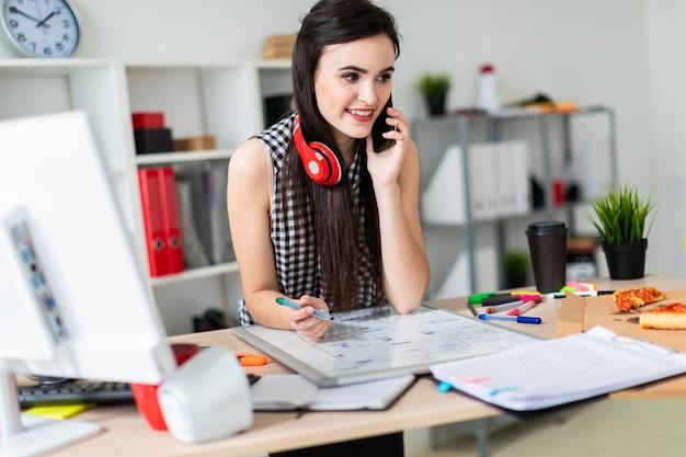 Młoda dziewczyna stoi przy stole, trzymając w dłoni zielony znacznik i rozmawia przez telefon. na szyi wiszą słuchawki dziewczyny.