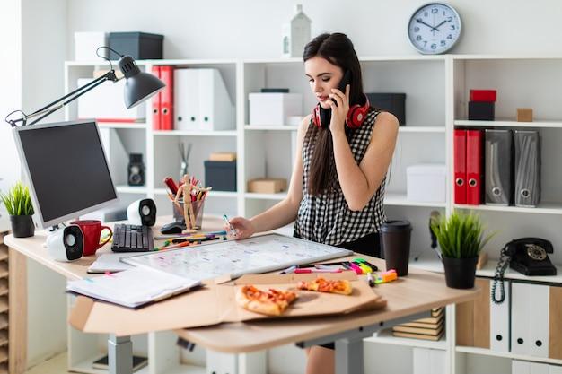 Młoda dziewczyna stoi przy stole, trzymając w dłoni zielony znacznik i rozmawiając przez telefon. na szyi wiszą słuchawki dziewczyny.