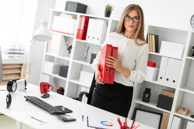 Młoda dziewczyna stoi przy stole w biurze i trzyma teczkę z dokumentami.