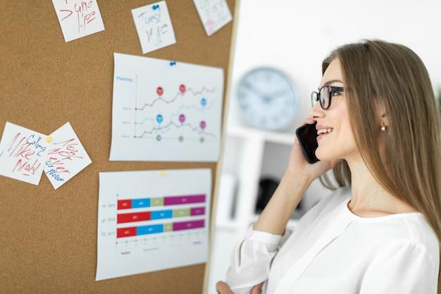 Młoda dziewczyna stoi przy tablicy z naklejkami i rozmawia przez telefon.
