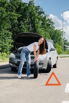 Młoda dziewczyna stoi przy zepsutym samochodzie na środku autostrady i próbuje zmienić złamane koło w upalny słoneczny dzień. awaria i awaria samochodu. czekam na pomoc.
