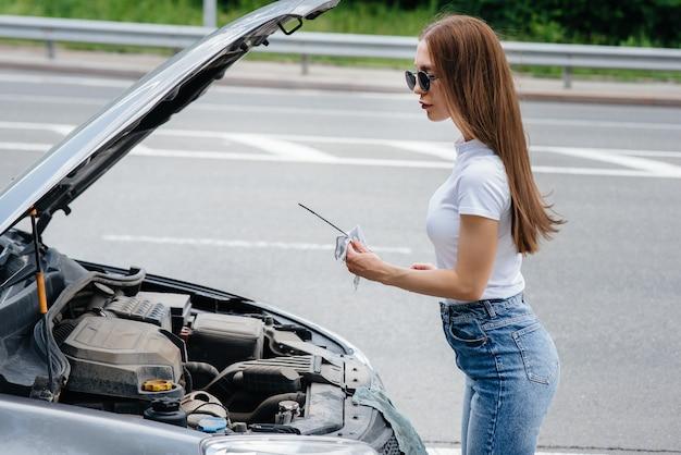 Młoda dziewczyna stoi przy zepsutym samochodzie na środku autostrady i sprawdza poziom oleju w silniku. awaria i awaria samochodu. czekam na pomoc.