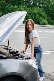 Młoda dziewczyna stoi przy zepsutym samochodzie na środku autostrady i zagląda pod maskę. awaria i awaria samochodu. czekam na pomoc.