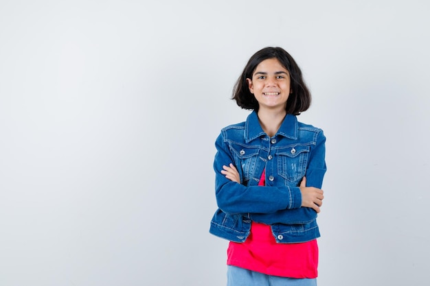 Młoda dziewczyna stoi rękami skrzyżowanymi w czerwonej koszulce i kurtce jeansowej i wygląda na szczęśliwą. przedni widok.