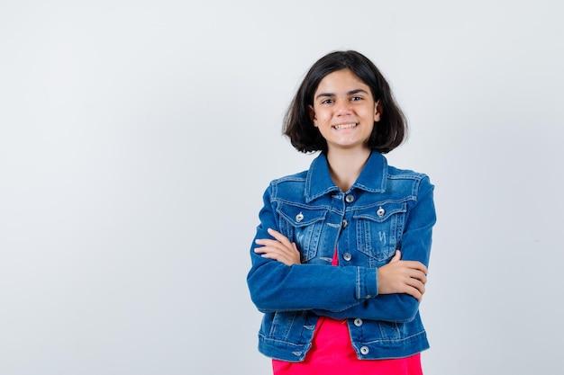 Młoda dziewczyna stoi rękami skrzyżowanymi w czerwonej koszulce i kurtce jeansowej i wygląda na szczęśliwą.
