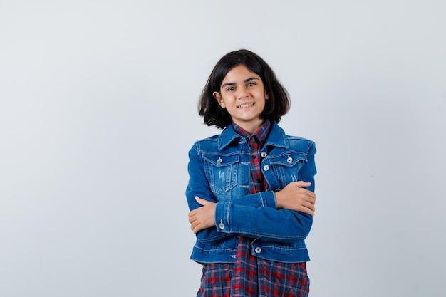 Młoda dziewczyna stoi skrzyżowanymi rękami w kraciastej koszuli i dżinsowej kurtce i wygląda ładnie, widok z przodu.
