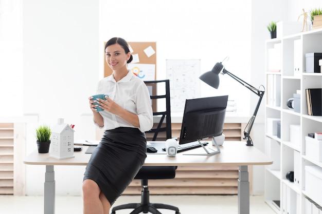 Młoda dziewczyna stoi w biurze i trzyma puchar