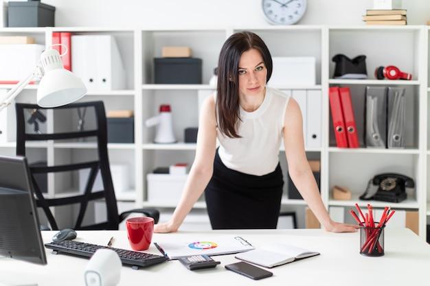 Młoda dziewczyna stoi w biurze przy biurku komputerowym.