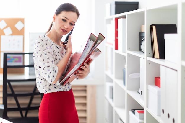 Młoda dziewczyna stoi w biurze, rozmawia przez telefon i trzyma folder z dokumentami.