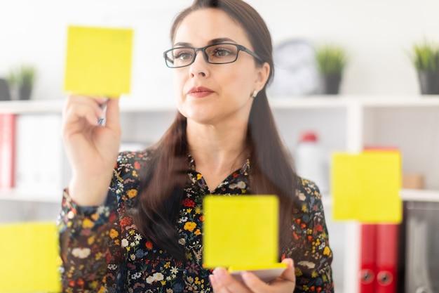 Młoda dziewczyna stoi w biurze w pobliżu przezroczystej płyty z naklejkami.