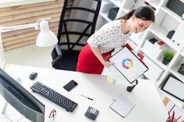 Młoda dziewczyna stoi w pobliżu biurka komputerowego w biurze i trzyma foldery i grafiki.