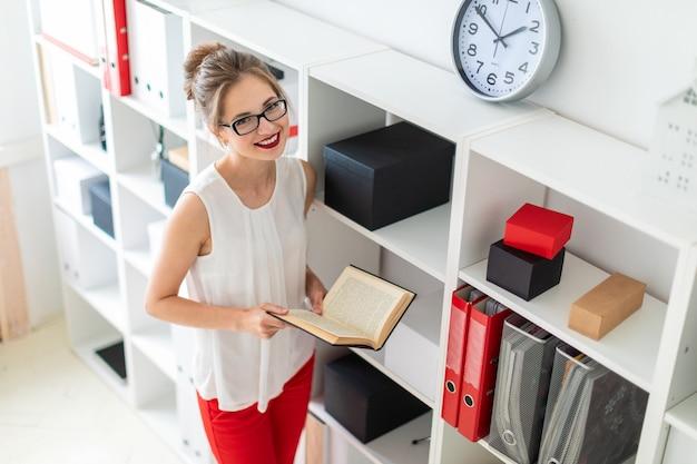 Młoda dziewczyna stoi w pobliżu półki i trzyma otwartą książkę w dłoniach.