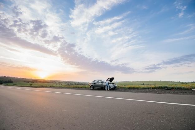 Młoda dziewczyna stoi w pobliżu zepsutego samochodu na środku autostrady o zachodzie słońca i próbuje go naprawić. awaria i naprawa samochodu. rozwiązywanie problemu.
