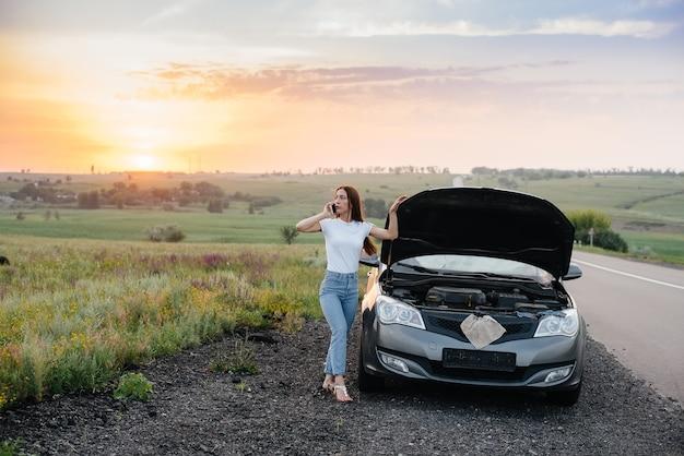 Młoda dziewczyna stoi w pobliżu zepsutego samochodu na środku autostrady o zachodzie słońca i próbuje wezwać pomoc przez telefon. awaria i naprawa samochodu. czekam na pomoc.