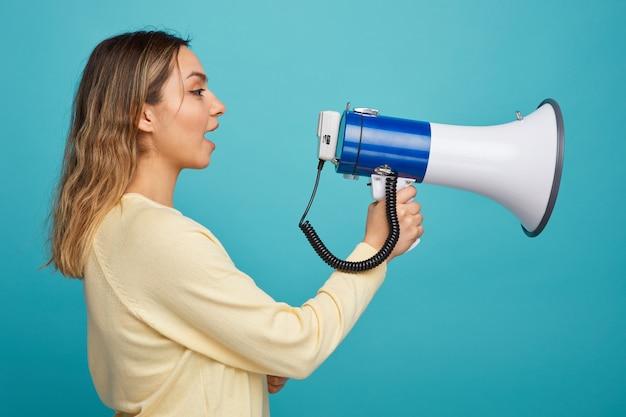 Młoda dziewczyna stoi w widoku profilu, patrząc na bok, rozmawiając przez głośnika
