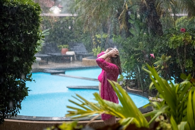 Młoda dziewczyna stoi z boku tropikalnego basenu w strugach deszczu.